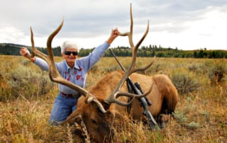woman posing with elk and horns
