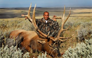 man in camo posing with elk and horns