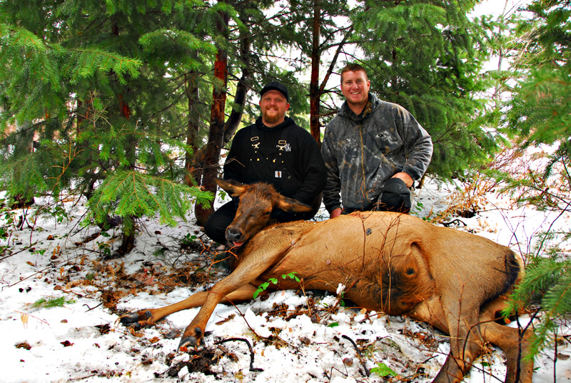 two men posing with elk