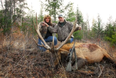 man and woman posing with elk and horns