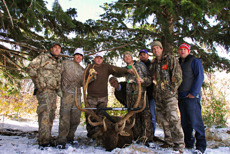 group posing with an elk and horns