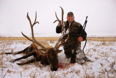 man posing with an elk and horns in winter snow