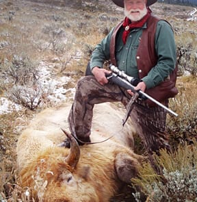 man posing with a buffalo