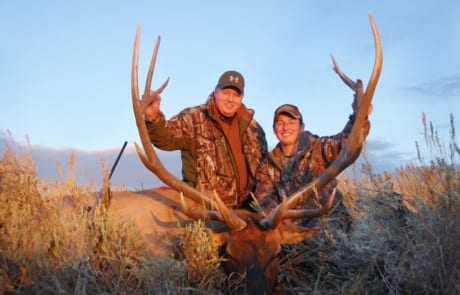 two men posing with an elk and horns