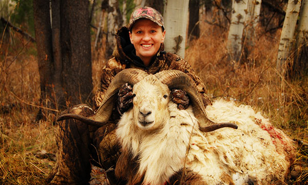 hunter posing with sheep with large horns